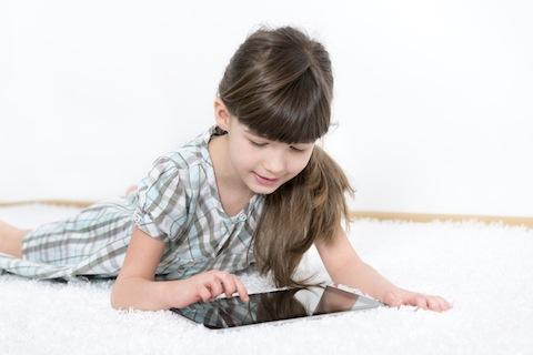 stock photo 23514521 kleines Mädchen spielt mit einem Tablet