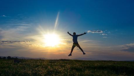 Silhouette Mann springt mit offenen Armen