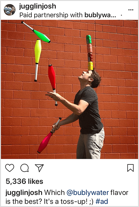 Josh Horton juggles clubs that match the colors of four Bubly water cans stacked on his head. The background is a red brick wall. The photo is an ad Josh created for Bubly water and posted in his Instagram feed with the description Which Bubly Water Flavor Is The Best? It's A Toss Up!