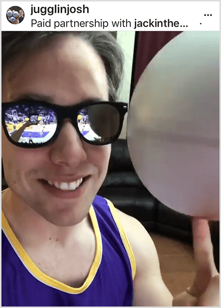 Josh Horton posts a photo for a campaign with Jack in the Box and the LA Lakers. Josh wears mirrored sunglasses and a Lakers jersey and is smiling for the camera while spinning a ball.