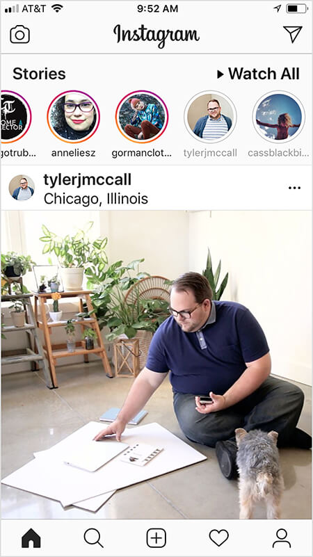 Tyler J. McCall has noticed that the Instagram algorithm seems to show a view more of an account's content in the feed if you watch or interact with the account's Instagram story and vice versa. A user's Instagram home screen shows a post from Tyler after the user has watched his story. The Instagram feed image shows Tyler sitting on the floor with large sheets of white paper and a notebook. A small black and tan dog faces Tyler. Lots of green plants on ladders are in the background.