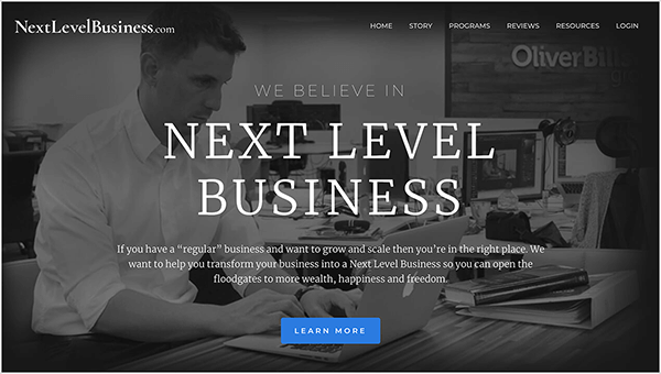 "This is a screenshot of the Next Level Business website, a business run by Oli Billson. In the upper left is the website name in white text, NextLevelBusiness.com. In the upper right are navigation options in white text. The options are Home, Story, Programs, Reviews Resources, and Login. In the center of the page, in white text, a heading says, ""We Believe in Next Level Business"". Below the heading is a short statement, ""If you have a 'regular' business and want to grow and scale then you're in the right place. We want to help you transform your business into a Next Level Business so you can open the floodgates to more wealth, happiness and freedom."" At the bottom of the page is a blue button with white text labeled ""Learn More"". The web page background is a black and white photo of a white man with short hair sitting at a desk typing on an Apple laptop. He's wearing a white button-down shirt and a watch on his left wrist. On the desk is a book stacked on top of a white binder. He's sitting in an open office environment with other desks and computers."