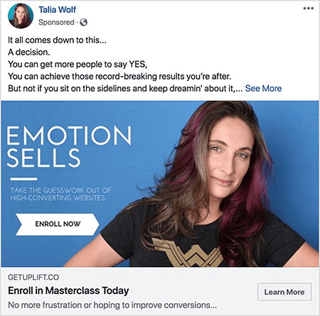 "This is a screenshot of a Facebook ad for a masterclass from Talia Wolf. In the ad text, each sentence is on a separate line. It says ""It all comes down to this . . . A decision. You can get more people to say YES. You can achieve those record-breaking results you're after. But not if you sit on the sidelines and keep dreamin' about it . . . "" After this text is a See More link. The ad image has a blue background with white text and a picture of Talia from the chest up. She is a white woman with brown and purple hair that falls below her shoulders. She's wearing a black t-shirt with a gold Wonder Woman logo. The text to the left of her photo says ""Emotion Sells"" and ""Take the guesswork out of high-converting websites"". Below this text is a white arrow with black text that says ""Enroll Now"". Below the image is the following headline and text: ""Getuplift.co"" and ""Enroll in Masterclass Today"" and ""No more frustration or hoping to improve conversions"". A Learn More button appears in the lower right."