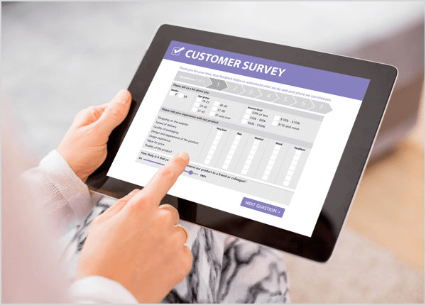 This is a photo of a tablet showing a customer survey on-screen. The hands of a white person are holding the tablet and tapping responses.