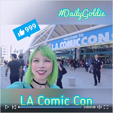 "This is a screenshot of a Goldie Chan LinkedIn video with a starter screen. The video was shot horizontally on a smartphone and turned into a square video with blurred letterboxing above and below the video. The starting video image shows Goldie in front of the convention center for LA Comic Con. Goldie appears from the shoulders up. She's an Asian woman with green hair. She's wearing makeup, a black choker necklace, and a turquoise shirt. In the letterbox area above the video, #DailyGoldie appears in a light green script font with a turquoise outline. A LinkedIn Like icon with the number 999 appears in a blue box over Goldie's head. In the letterbox area below the video, the text ""LA Comic Con"" appears in a light green san serif font with a turquoise outline."