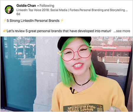 "This is a screenshot of Goldie Chan sharing a video with a clear takeaway. The text above the video says "" 5 Strong LinkedIn Personal Brands Let's review 5 great personal brands that have developed into matur. . . see more"". In the video image, Goldie appears from the chest up. She's an Asian woman with green hair. She's wearing makeup, a black choker necklace, and a yellow shirt. A video filter makes it look like she's wearing red glasses sketched with a marker."