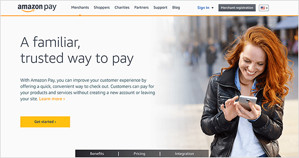 "This is a screenshot of the Amazon Pay webpage. It has a white background and black text. The navigation options at the top are Merchants, Shoppers, Charities, Partners, Support, and Blog. A Sign In link and black Merchant Registration button also appear. In the main area of the web page, a heading and some other text appears on the right. The heading says ""A familiar, trusted way to pay."" A yellow button labeled Get Started appears below the heading. On the right is a photo of a white woman with long red hair. She is standing and looking at her smartphone. She's smiling and wearing and black jacked and button down shirt."