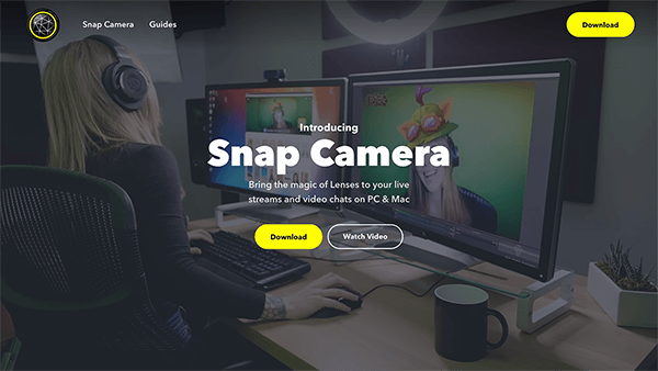 "This is a screenshot of the Snap Camera website. In the page background a woman sits at a desktop computer with headphones on, using an augmented reality lens to make it seems like she's wearing a silly, cartoonish hat. The white text in the center of the page says ""Bring the magic of Lenses to your live streams and video chats on PC and Mac."" A yellow button is labeled Download."