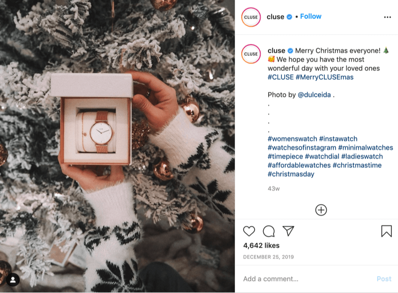 instagram post from @cluse showing a picture of a snowflake-sweatered model holding a watch in front of a snowy tree by @dulceida with the hashtags #cluse and #merryclusemas